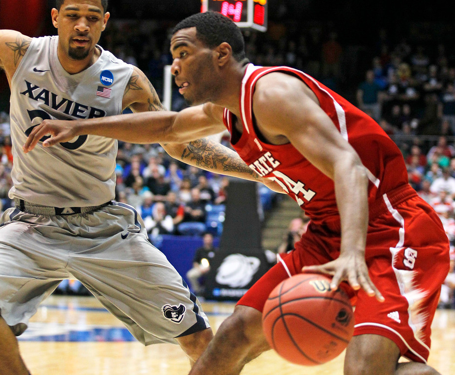 . North Carolina State forward T.J. Warren (24) drives against Xavier forward Justin Martin during the first half of a first-round game of the NCAA college basketball tournament, Tuesday, March 18, 2014, in Dayton, Ohio. (AP Photo/Skip Peterson)