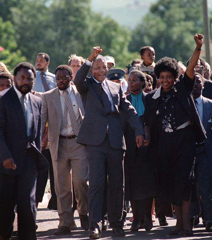 """. A picture taken on February 11, 1990 shows Nelson Mandela (C) and his then-wife Winnie raising their fists and saluting cheering crowd upon Mandela\'s release from the Victor Verster prison near Paarl. Rolihlahla Dalibhunga Mandela, affectionately known by his clan name \""""Madiba\"""", became commander-in-chief of Umkhonto weSizwe (Spear of the Nation), the armed underground wing of the African National Congress, in 1961, and the following year underwent military training in Algeria and Ethiopia. After more than a year underground, Mandela was captured by police and sentenced in 1964 to life in prison during the Rivonia trial, where he delivered a speech that was to become the manifesto of the anti-apartheid movement. Mandela started his prison years in the notorious Robben Island Prison, a maximum security prison on a small island 7Km off the coast near Cape Town. In April 1984 he was transferred to Pollsmoor Prison in Cape Town and in December 1988 he was moved the Victor Verster Prison near Paarl. While in prison, Mandela flatly rejected offers made by his jailers for remission of sentence in exchange for accepting the bantustan policy by recognizing the independence of the Transkei and agreeing to settle there. Again in the \'eighties Mandela rejected an offer of release on condition that he renounce violence. Prisoners cannot enter into contracts. Only free men can negotiate, he said, according to ANC reports. ( ALEXANDER JOE/AFP/Getty Images)"""