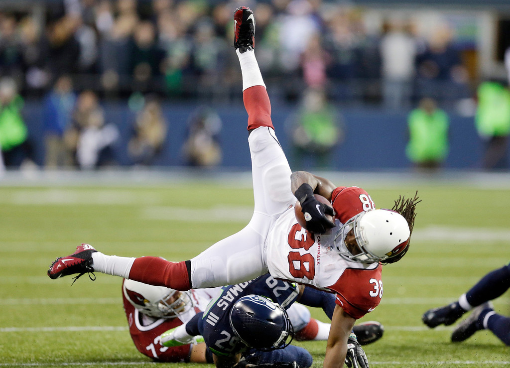 . Arizona Cardinals\' Andre Ellington, top, flips on a run while being brought down by the Seattle Seahawks in the second half of an NFL football game, Sunday, Dec. 22, 2013, in Seattle. Arizona won 17-10. (AP Photo/Elaine Thompson)