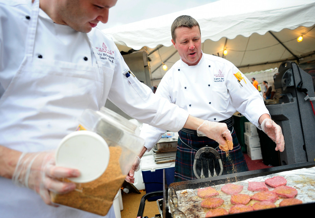 . Warwick Denver Hotel sous chef Chris Blackwell (L) and executive chef Jesper Jonsson (R), prepare food behind during the A Taste of Colorado festival at Civic Center Park in Denver, Colorado, Saturday, August 30, 2014. Jonsson was sporting the kilt for a cook-off later in the evening.  (Photo By Brenden Neville / Special to The Denver Post)