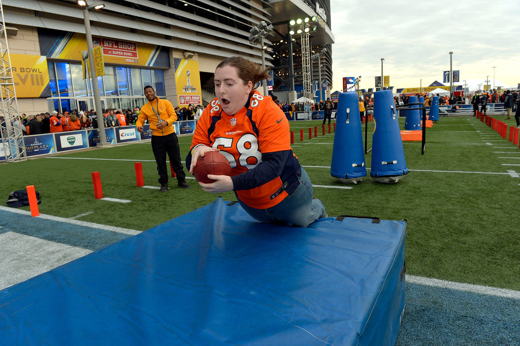 . Broncos fan Allison Kasic, a former Coloradoan, now from Washington, DC scores a touchdown while playing a game for the fans outside of the stadium prior to the start of the game.  The Denver Broncos vs the Seattle Seahawks in Super Bowl XLVIII at MetLife Stadium in East Rutherford, New Jersey Sunday, February 2, 2014. (Photo by Craig Walker/The Denver Post)