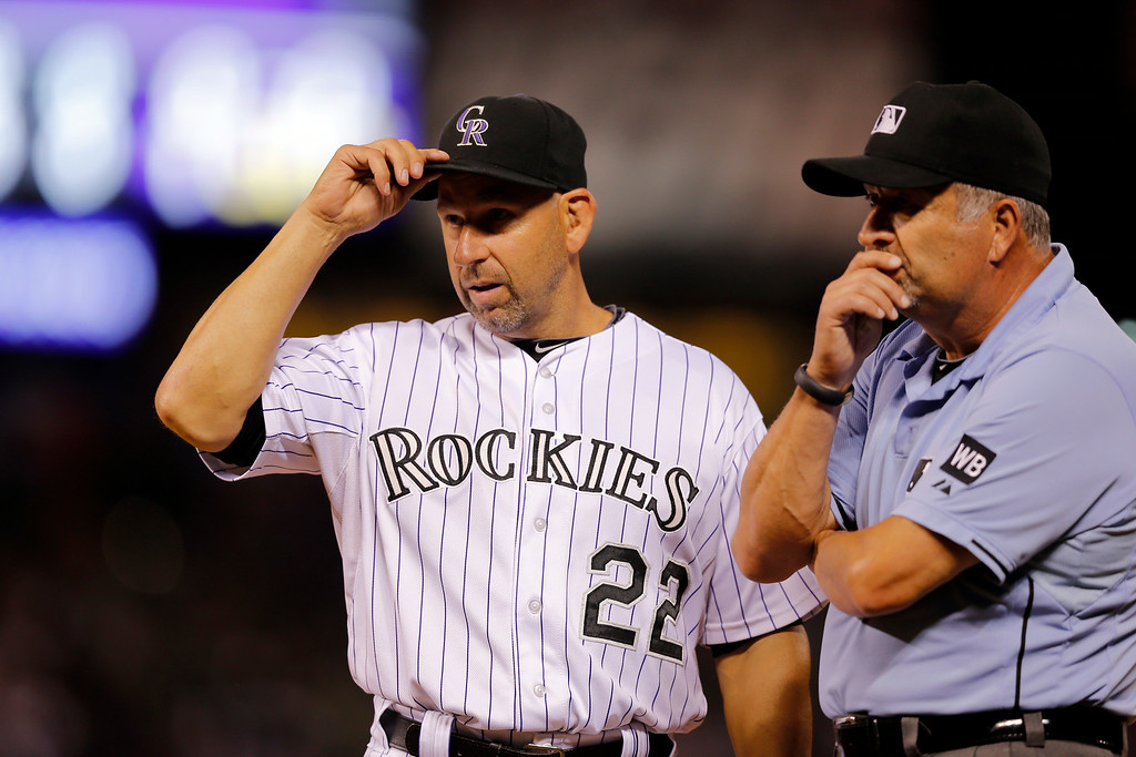 . Umpire Dale Scott listens as Colorado Rockies manager Walt Weiss questions a call at first during the sixth inning of a baseball game against the Cincinnati Reds on Friday, Aug. 15, 2014, in Denver. (AP Photo/Jack Dempsey)
