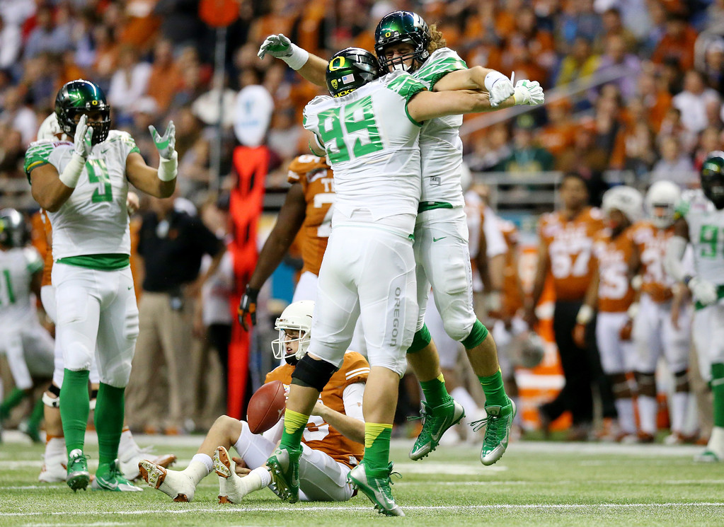 . Linebacker Joe Walker #35 of the Oregon Ducks celebrates with defensive lineman Sam Kamp #99 after sacking quarterback Case McCoy #6 of the Texas Longhorns during the Valero Alamo Bowl at the Alamodome on December 30, 2013 in San Antonio, Texas.  (Photo by Ronald Martinez/Getty Images)