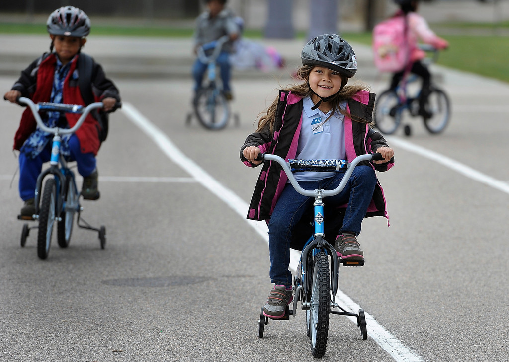 . DENVER, CO - Oct. 11: Maria Magallanes, 6, right, joins her classmates for a spin on the school blacktop. Wish for Wheels and its volunteers build and give away over one hundred bikes to kindergarteners and first-graders at Smith Renaissance School in Park Hill. Wish for Wheels says its goal with one-in-five children liven in poverty, is to give as many kids as possible their first brand new bike and helmet. (Photo By Kathryn Scott Osler/The Denver Post)