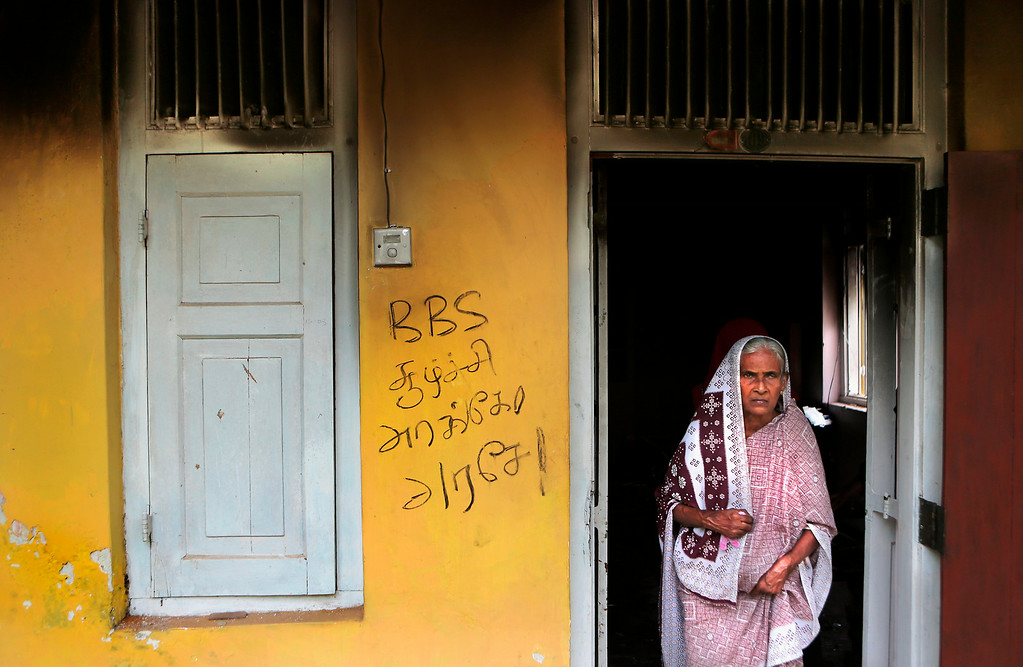 ". In this Wednesday, June 25, 2014 photo, a Sri Lankan Muslim woman stands at the doorway of a vandalized house in Darga Town, in Aluthgama about 50 kilometers (31 miles) south of Colombo, Sri Lanka. The onslaught by the Bodu Bala Sena (BBS), a hardline Buddhist group, killed two Muslims in the worst religious violence Sri Lanka has seen in decades. Graffiti on the wall reads: ""Is this BBS conspiracy?\"" (AP Photo/Eranga Jayawardena)"