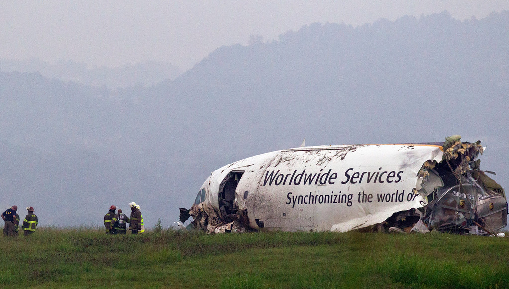 . A UPS cargo plane lies on a hill at Birmingham-Shuttlesworth International Airport after crashing on approach, Wednesday, Aug. 14,  2013, in Birmingham, Ala. Toni Herrera-Bast, a spokeswoman for Birmingham\'s airport authority, says there are no homes in the immediate area of the crash. (AP Photo/Butch Dill)