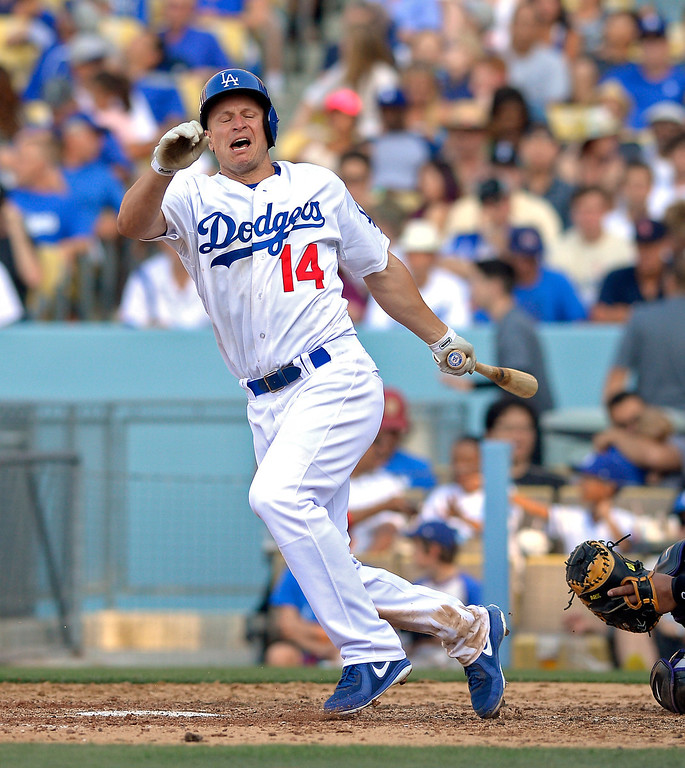 . Los Angeles Dodgers\' Mark Ellis reacts after being hit with a foul tip during the eighth inning of the Dodgers\' baseball game against the Colorado Rockies, Saturday, July 13, 2013, in Los Angeles. Ellis was later taken out of the game. (AP Photo/Mark J. Terrill)