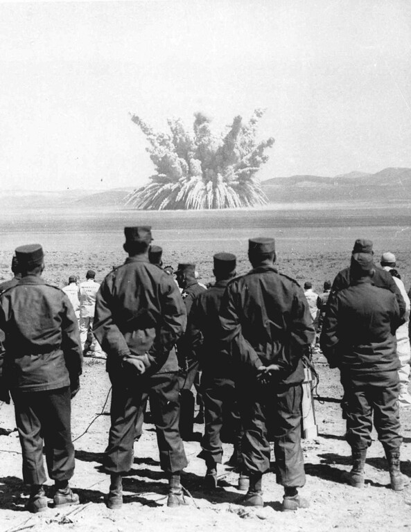 . Observers watch an atomic nuclear blast in this March 23, 1955 file photo. The National Cancer Institute said Friday, August 1, 1997 that fallout from 1950s nuclear bomb tests exposed millions of children across the country to radioactive iodine, raising the possibility that 10,000 to 75,000 of them might develop thyroid cancer. But government doctors emphasized they have no proof this radioactive substance causes thyroid cancer, so their estimate is a worst-case scenario. Nobody was tested in the NCI study. (AP Photo/File)
