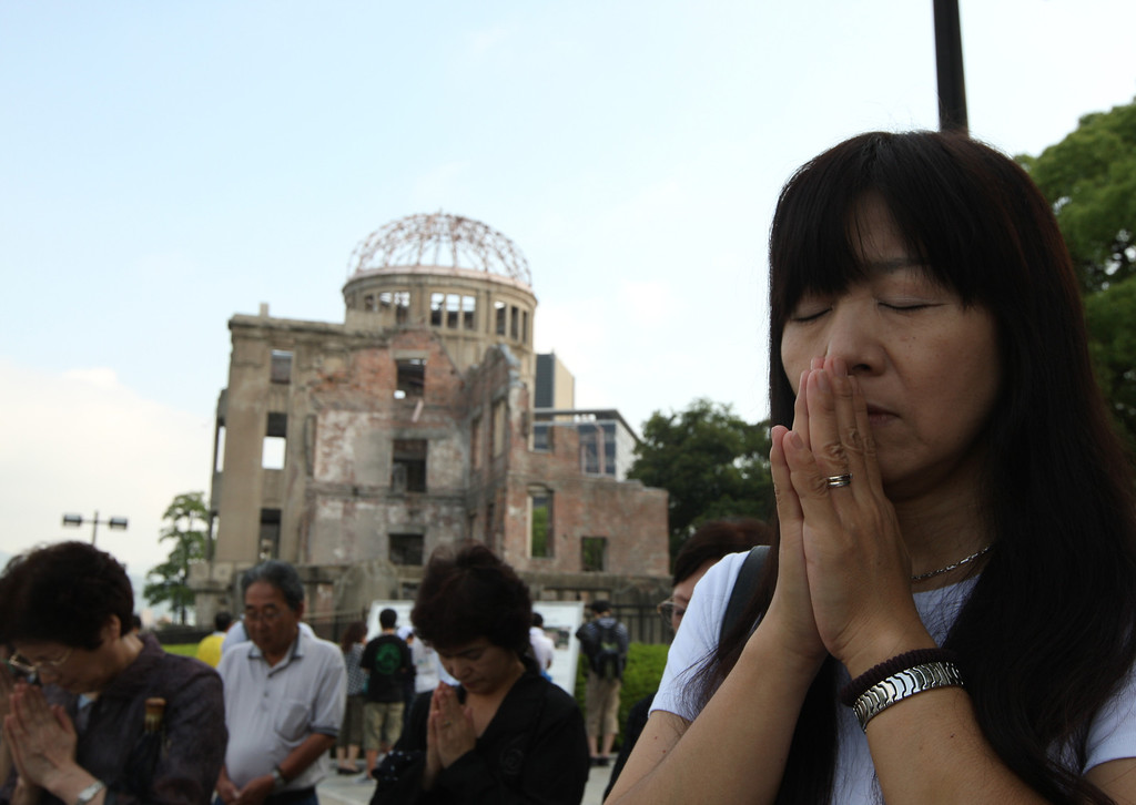. Japanese people pray for atomic bomb victims in front of a  Atomic Bomb Dome at the Hiroshima Peace Memorial Park on the day of the 68th anniversary of the atomic bombing of Hiroshima on August 6, 2013 in Hiroshima, Japan.  (Photo by Buddhika Weerasinghe/Getty Images)