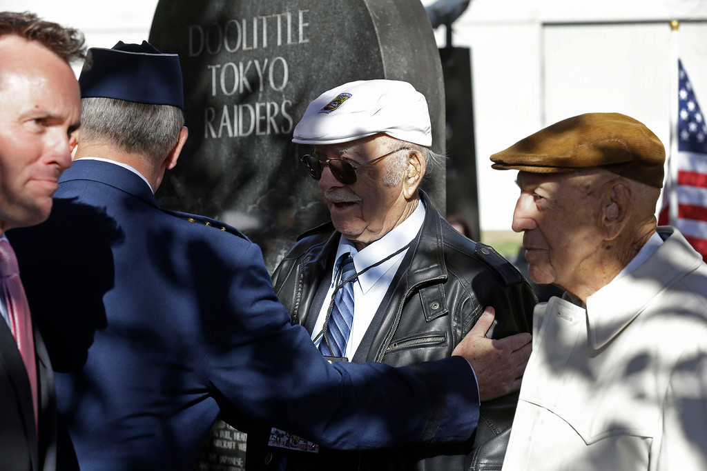 . Two of the four surviving members of the 1942 raid on Tokyo led by Lt. Col. Jimmy Doolittle, Edward Saylor, center, and Richard Cole, right, are thanked by Gen. Mark Welsh III, Chief of Staff of the US Air Force, and Eric Fanning, left, acting Secretary of the US Air Force, Saturday, Nov. 9, 2013, at a monument marking the raid at the National Museum of the US Air Force in Dayton, Ohio. (AP Photo/Al Behrman)