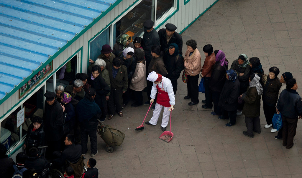 . A food shop keeper sweeps with a broom while people line up outside a shop window in Pyongyang, North Korea, Tuesday, April 16, 2013. (AP Photo/Alexander F. Yuan)