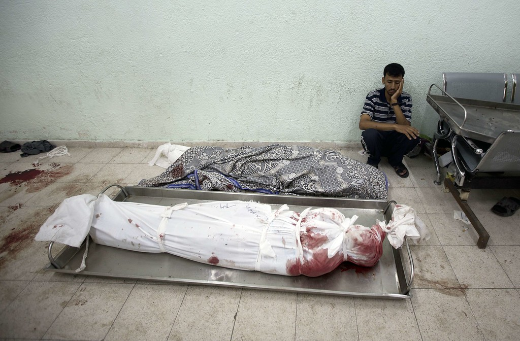 """. A Palestinian who lost relatives in an Israeli strike on a compound housing a UN school in Jabalia refugee camp in the northern Gaza Strip, mourns next to bodies wrapped in shrouds at the Kamal Edwin hospital in Beit Lahia where victims from the attack were brought early on July 30, 2014. Israeli bombardments early on July 30 killed \""""dozens\"""" Palestinians in Gaza, including at least 16 at a UN school, medics said, on day 23 of the Israel-Hamas conflict. AFP PHOTO / MAHMUD HAMS/AFP/Getty Images"""