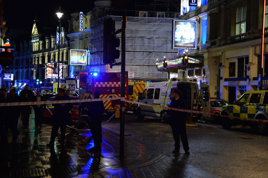 . Police and emergency services personnel assist in operations behind a cordon following a ceiling collapse at a theatre in Central London on December 19, 2013.   The ceiling of a top London theatre collapsed on the audience during a performance Thursday, causing what police said was an unknown number of casualties and leaving terrified theatergoers covered in blood and dust.  AFP PHOTO/LEON NEAL/AFP/Getty Images