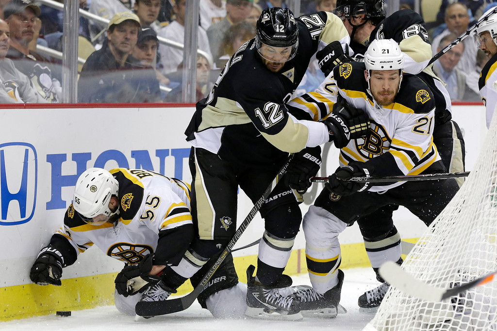 . Pittsburgh Penguins\' Jarome Iginla (12) is caught between Boston Bruins\' Johnny Boychuk (55) and Andrew Ference (21) behind the net during the second period of Game 2 of the NHL hockey Stanley Cup playoffs Eastern Conference finals, in Pittsburgh on Monday, June 3, 2013. (AP Photo/Gene J. Puskar)