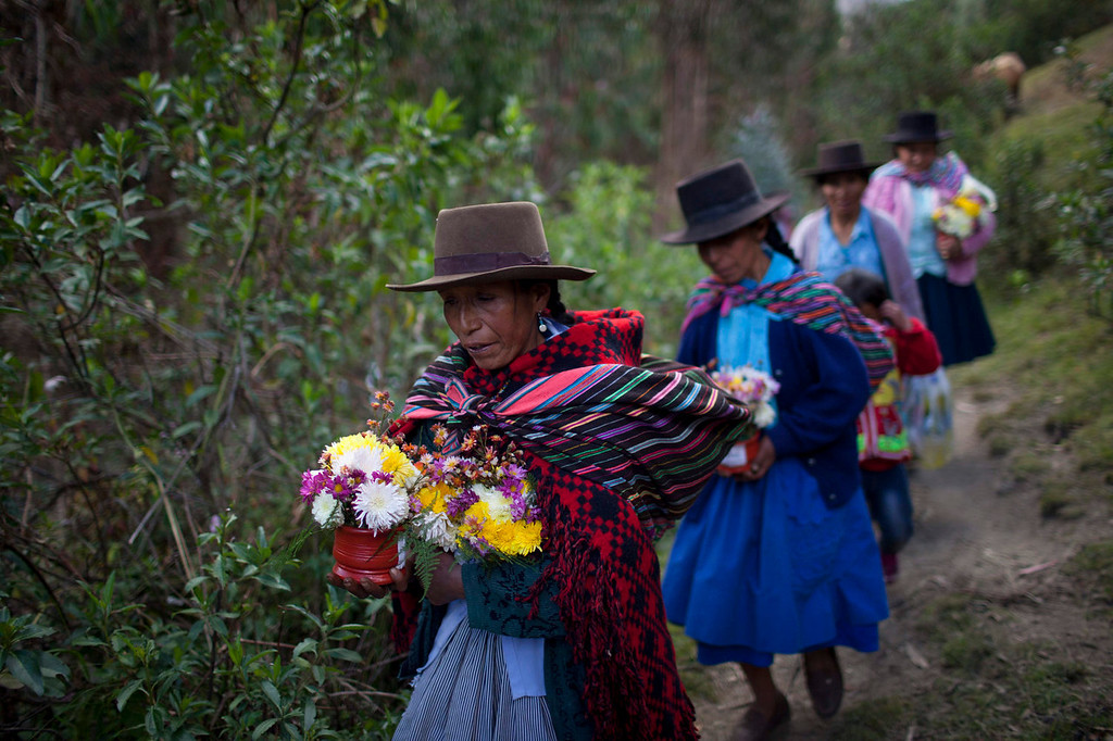 . Relatives bearing flowers walk to the cemetery to attend a mass burial in Chaca, Peru. Family and friends attended the mass burial of the Chaca residents who were tortured and killed in a Jan. 8, 1988 massacre by Shining Path militants in retaliation for forming a self-defense committee. As weapons, the victims had little more than slingshots and poles with knives affixed.   (AP Photo/Rodrigo Abd)