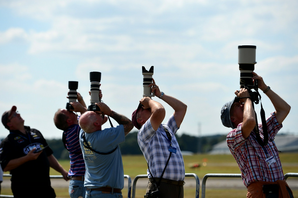 . Airplane enthusiasts photograph an air display on the second day of the Farnborough International Air show in Hampshire, England, on July 15, 2014. AFP PHOTO / CARL COURT/AFP/Getty Images