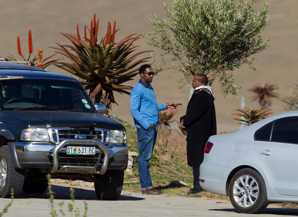 . Grandson Ndaba Mandela (L) speaks with an unidentified man at an area within the property of former South African President Nelson Mandela\'s house in Qunu, June 25, 2013. South Africans adopted a mood of sombre resignation on Monday to the inevitability of saying goodbye to former president Mandela after the 94-year-old anti-apartheid leader\'s condition in hospital deteriorated to critical. REUTERS/Rogan Ward