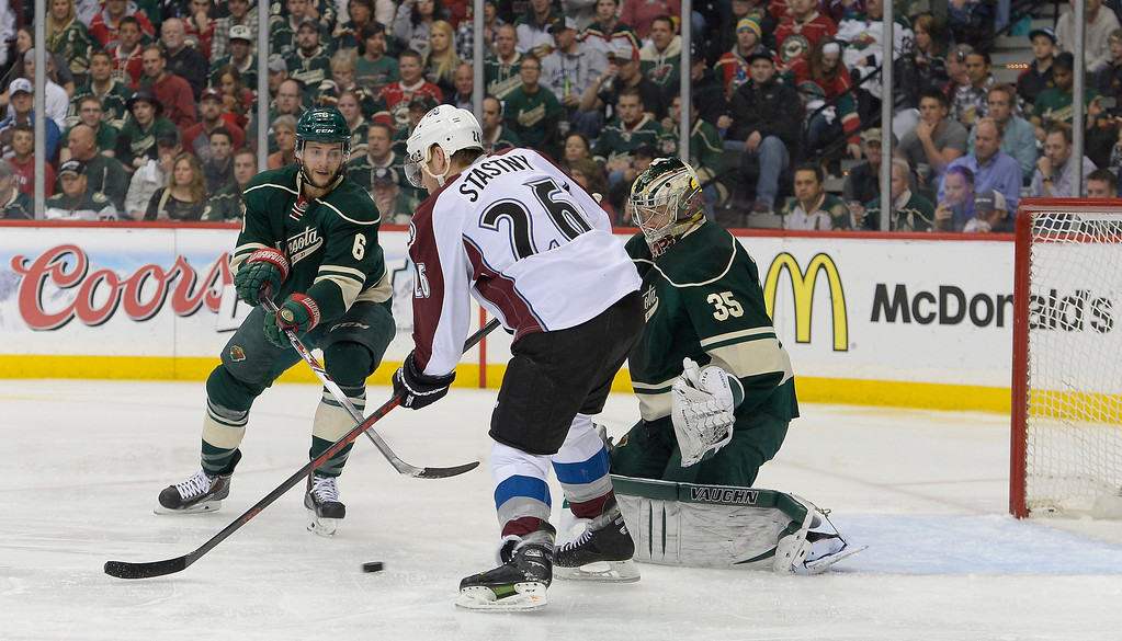 . Colorado Avalanche center Paul Stastny (26) tries to defect a shot on Minnesota Wild goalie Darcy Kuemper (35) during the first period April 24, 2014 at Xcel Energy Center. Minnesota Wild defenseman Marco Scandella (6) is also in on defense. (Photo by John Leyba/The Denver Post)