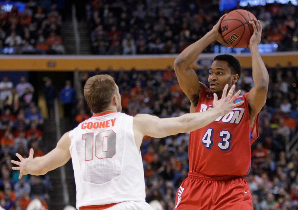 . Dayton\'s Vee Sanford (43) looks to pass away from Syracuse\'s Trevor Cooney (10) during the first half of a third-round game in the NCAA men\'s college basketball tournament in Buffalo, N.Y., Saturday, March 22, 2014. (AP Photo/Bill Wippert)