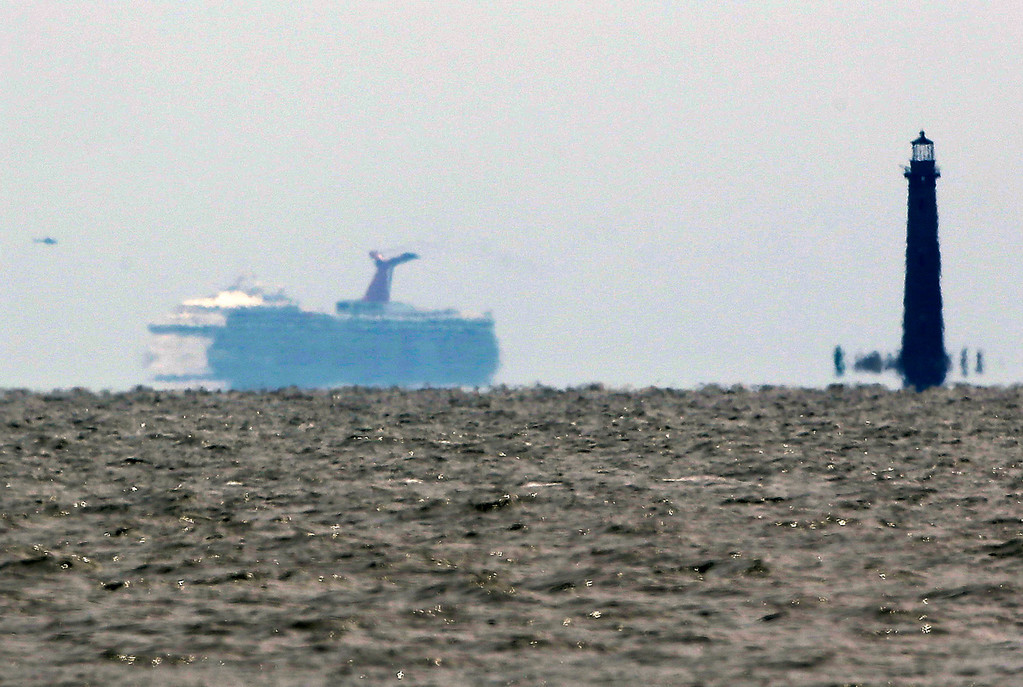 . The cruise ship Carnival Triumph is visible several miles beyond the Sand Island Light House near Dauphin Island, Ala., Thursday, Feb. 14, 2013. The ship with over 1,000 passengers aboard has been idled for nearly a week in the Gulf of Mexico following an engine room fire, and is being towed to port in Mobile, Ala. (AP Photo/Dave Martin)