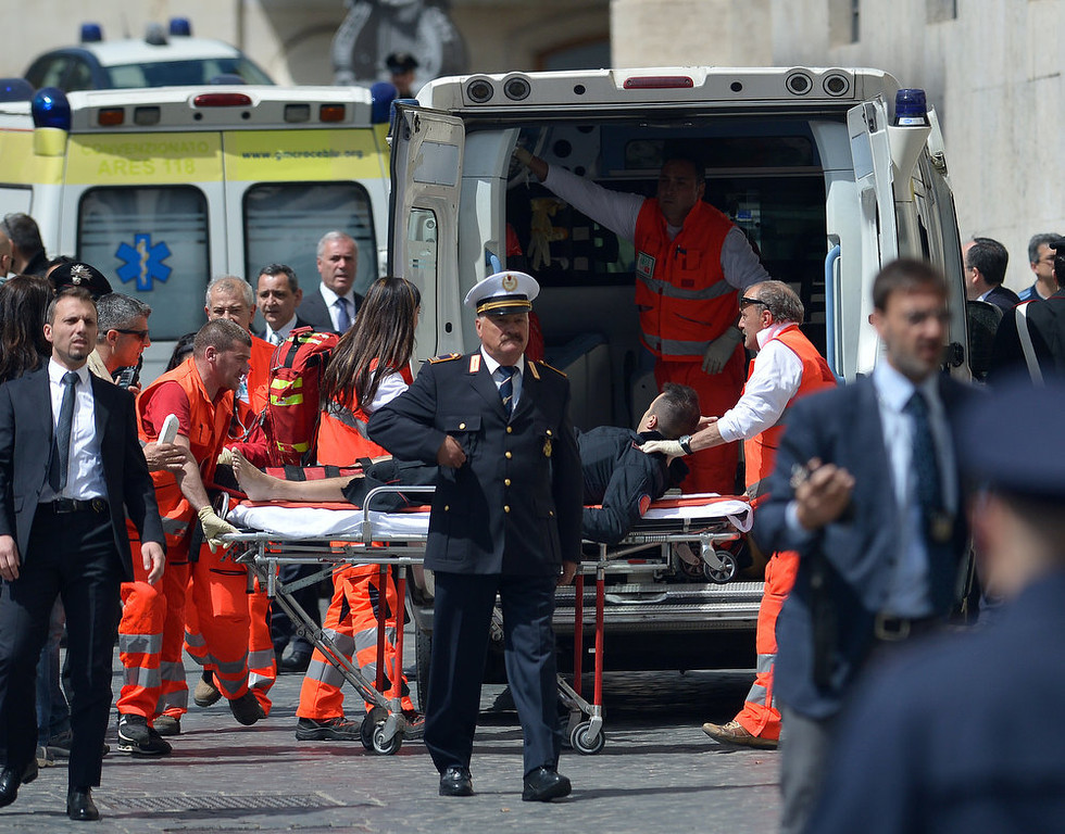. An Italian policeman is carried away by paramedics after two policemen were wounded on April 28, 2013 during a shooting outside the palazzo Chigi, the Italian Prime minister offices, as the country\'s new ministers were being sworn in. GABRIEL BOUYS/AFP/Getty Images