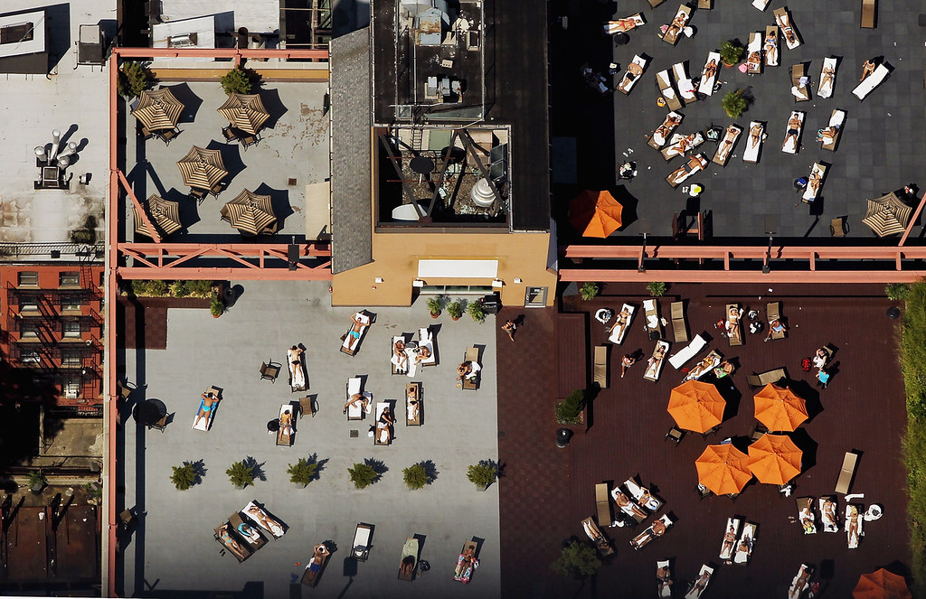 . An aerial view of New Yorkers taking in the sun on Manhattan rooftops on August 4, 2012 in New York City. The past year through June 2012 in the continental United States has been the hottest since modern record-keeping started in 1895, according to the National Oceanic and Atmospheric Administration (NOAA). NOAA also reports the ten warmest years since 1895 have occurred since 2000. A weather expert at the agency suggested climate change has a role in the high temperatures. (Photo by Mario Tama/Getty Images)