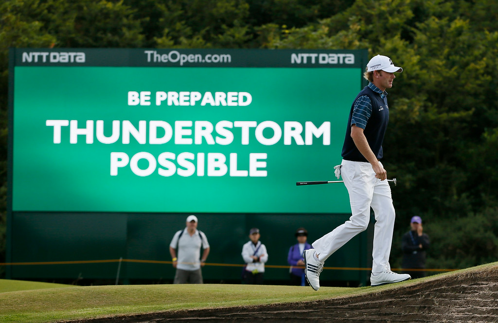 . Brandt Snedeker of the US walks past a digital sign showing a weather warning on the second day of the British Open Golf championship at the Royal Liverpool golf club, Hoylake, England, Friday July 18, 2014. (AP Photo/Alastair Grant)