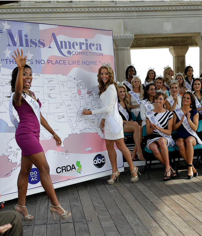 . Miss Tennessee Shelby Thompson signs a map as Miss Texas Ivana Hall, waves while other Miss America contestants applaud during introductions after arriving in Atlantic City, N.J. on Tuesday, Sept. 3, 2013. The Miss America pageant is back in the city where it began, six years after spurning the city for Las Vegas. The pageant held a welcoming ceremony Tuesday for the 53 contestants, one from each state plus the District of Columbia, Puerto Rico and the U.S. Virgin n Islands. The contestants filed out of Boardwalk Hall, where the competition will begin next week and culminate days later, and walked across the Boardwalk to a stage. (AP Photo/Mel Evans)