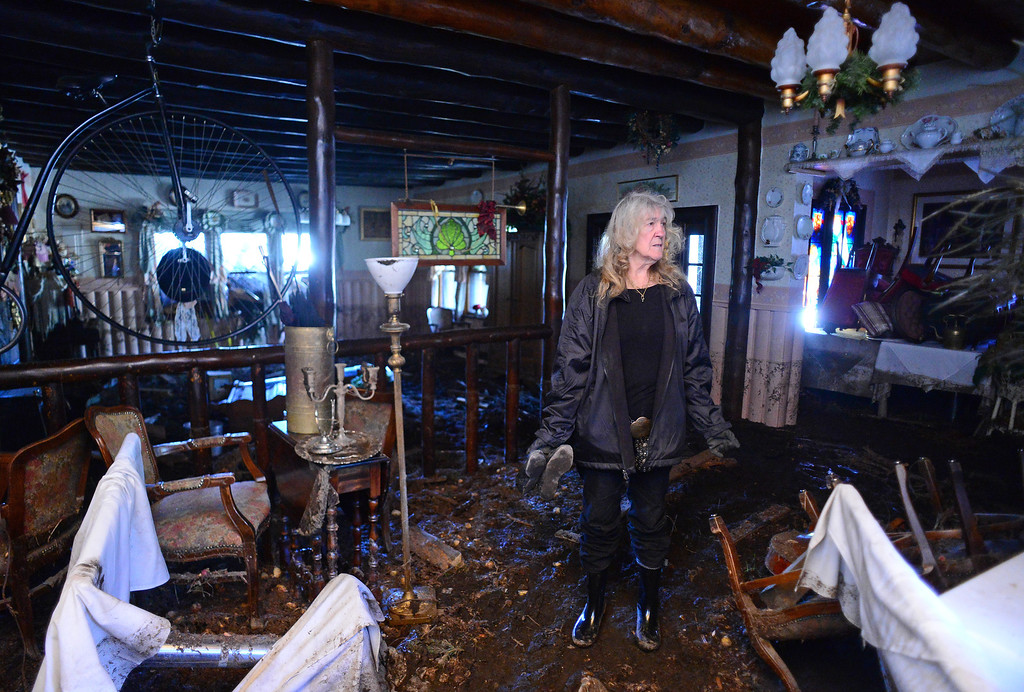 . GLEN HAVEN, CO - OCTOBER 8: Glen Haven Inn owner Sheila Sellers looks at what remains on the inside of their historic Glen Haven Inn in Glen Haven, CO on October 8, 2013.  The Inn was one of the only businesses that actually made it in the town but has been inundated with mud and debris.  The water line along the walls suggest that the flood waters reached at least four feet inside the building. (Photo By Helen H. Richardson/ The Denver Post)
