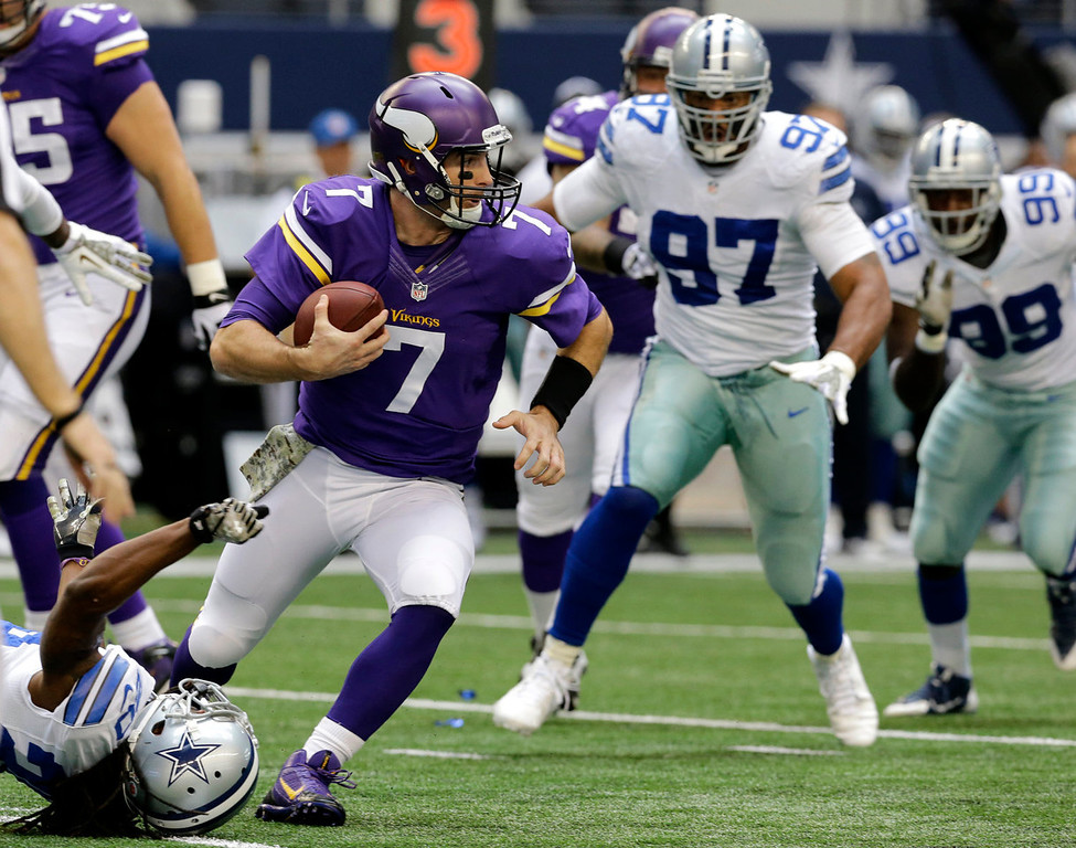 . Minnesota Vikings quarterback Christian Ponder (7) keeps the ball and runs under pressure from Dallas Cowboys\' B.W. Webb, bottom, Jason Hatcher (97) and Tyrone Crawford (98) in the first half of an NFL football game, Sunday, Nov. 3, 2013, in Arlington, Texas. (AP Photo/Nam Y. Huh)