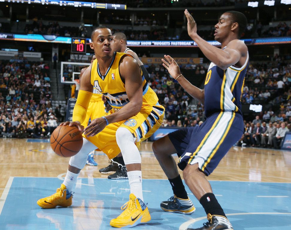. Denver Nuggets guard Randy Foye, left, works ball inside for shot as Utah Jazz guard Alec Burks covers in the first quarter of an NBA basketball game in Denver on Saturday, April 12, 2014. (AP Photo/David Zalubowski)