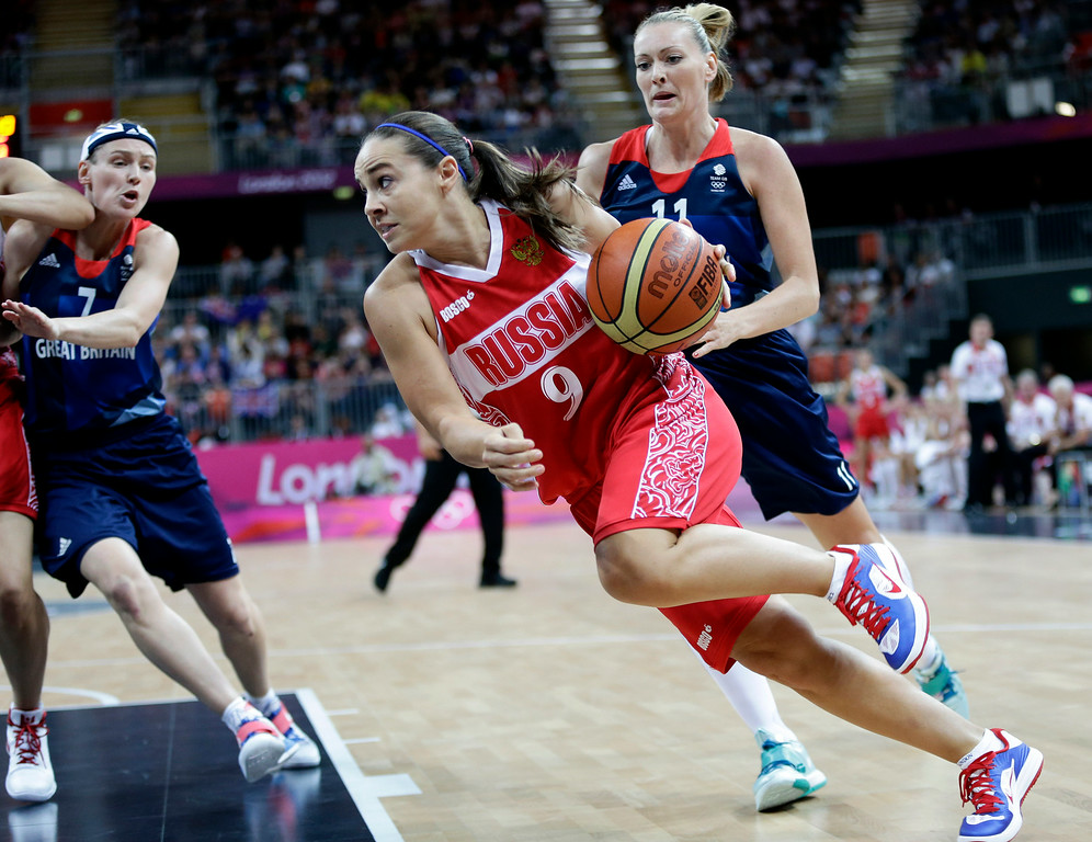 . Russia\'s Becky Hammon (9) drives the ball past Russia\'s Marina Kuzina (7) and  Natalya Vieruduring a preliminary women\'s basketball game at the 2012 Summer Olympics, Wednesday, Aug. 1, 2012, in London. (AP Photo/Eric Gay)