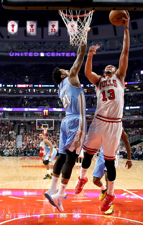 . Chicago Bulls center Joakim Noah (13) shoots over Denver Nuggets forward Wilson Chandler (21) during the first half of an NBA basketball game Friday, Feb. 21, 2014, in Chicago. (AP Photo/Charles Rex Arbogast)
