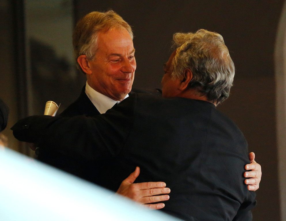 . Former British Prime Minister Tony Blair, left, is greeted after arriving for the memorial service for former South African president Nelson Mandela at the FNB Stadium in Soweto near Johannesburg, Tuesday, Dec. 10, 2013. (AP Photo/Ben Curtis)