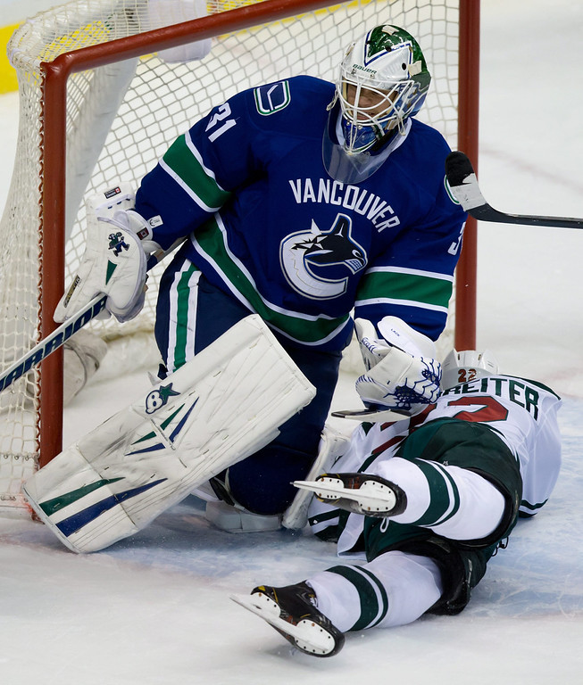 . Minnesota Wild\'s Nino Niederreiter, right, of Switzerland, crashes into Vancouver Canucks goalie Eddie Lack, of Sweden, during the second period of an NHL hockey game Friday, Feb. 28, 2014, in Vancouver, British Columbia. (AP Photo/The Canadian Press, Darryl Dyck)