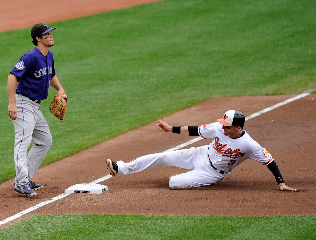 . Baltimore Orioles\' Ryan Flaherty (3) slides into third against Colorado Rockies third baseman Nolan Arenado, left, on a single by Alexi Casilla during the second inning of a baseball game on Sunday, Aug. 18, 2013, in Baltimore. (AP Photo/Nick Wass)
