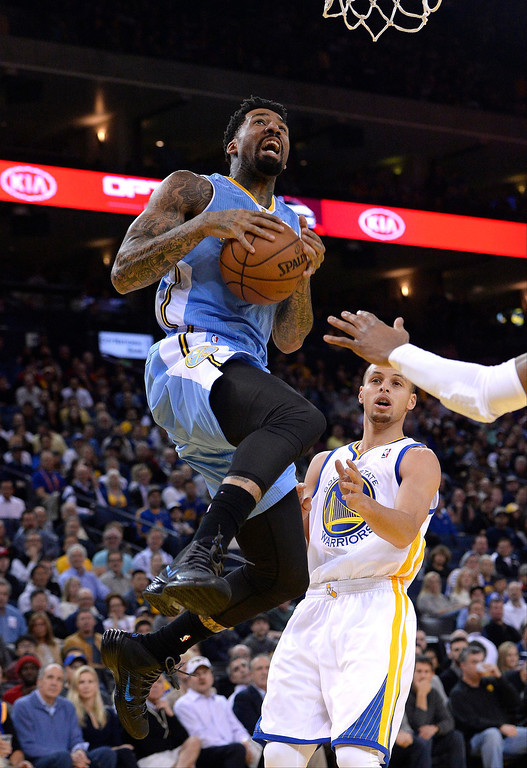 . Denver Nuggets small forward Wilson Chandler (L) goes to the basket as Golden State Warriors point guard Stephen Curry (R) looks on during the first half.  EPA/JOHN G. MABANGLO CORBIS OUT