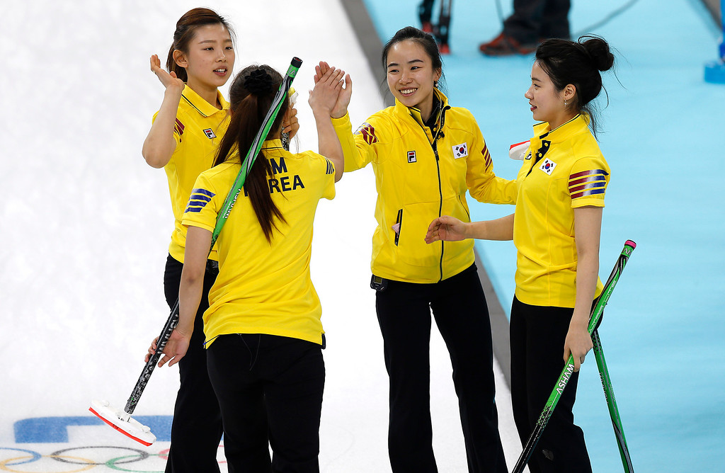 . South Korean women\'s curling team from left to right, Lee Seulbee, Gim Un-chi, Kim Jisun and Um Min-ji, celebrate after beating the Russian team at the women\'s curling competition at the 2014 Winter Olympics, Thursday, Feb. 13, 2014, in Sochi, Russia. (AP Photo/Wong Maye-E)