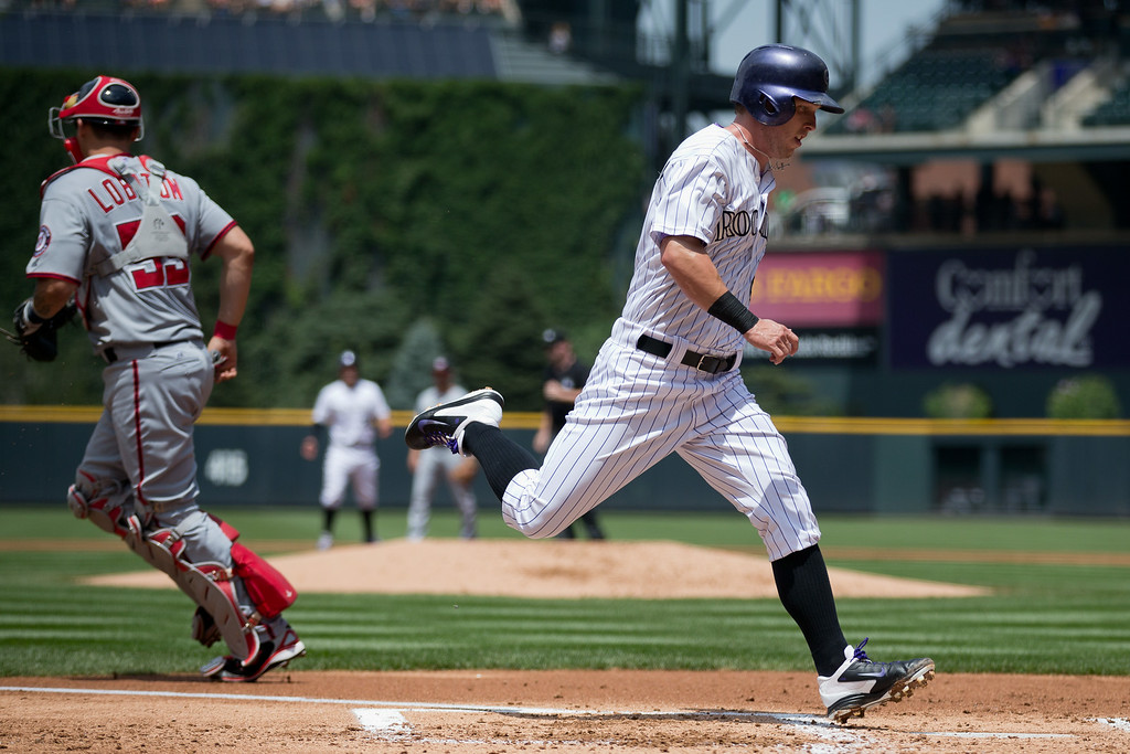 . DENVER, CO - JULY 23:  Corey Dickerson #6 of the Colorado Rockies strides in to score as catcher Jose Lobaton #59 of the Washington Nationals tries to make a play on the baseball during the first inning at Coors Field on July 23, 2014 in Denver, Colorado. (Photo by Justin Edmonds/Getty Images)