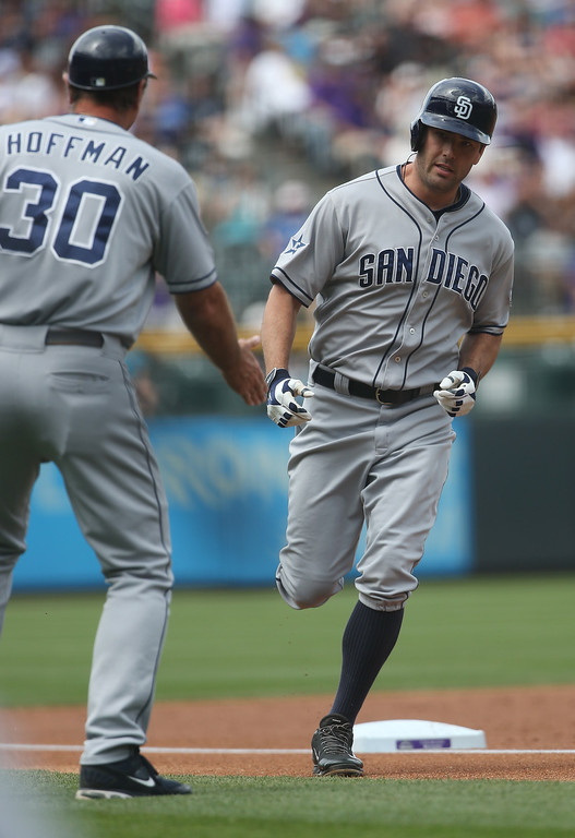 . San Diego Padres\' Seth Smiith, right, is congratulated as he circles the bases after hitting a solo home run by third base coach Glenn Hoffman against the Colorado Rockies in the first inning of a baseball game in Denver on Sunday, May 18, 2014. (AP Photo/David Zalubowski)