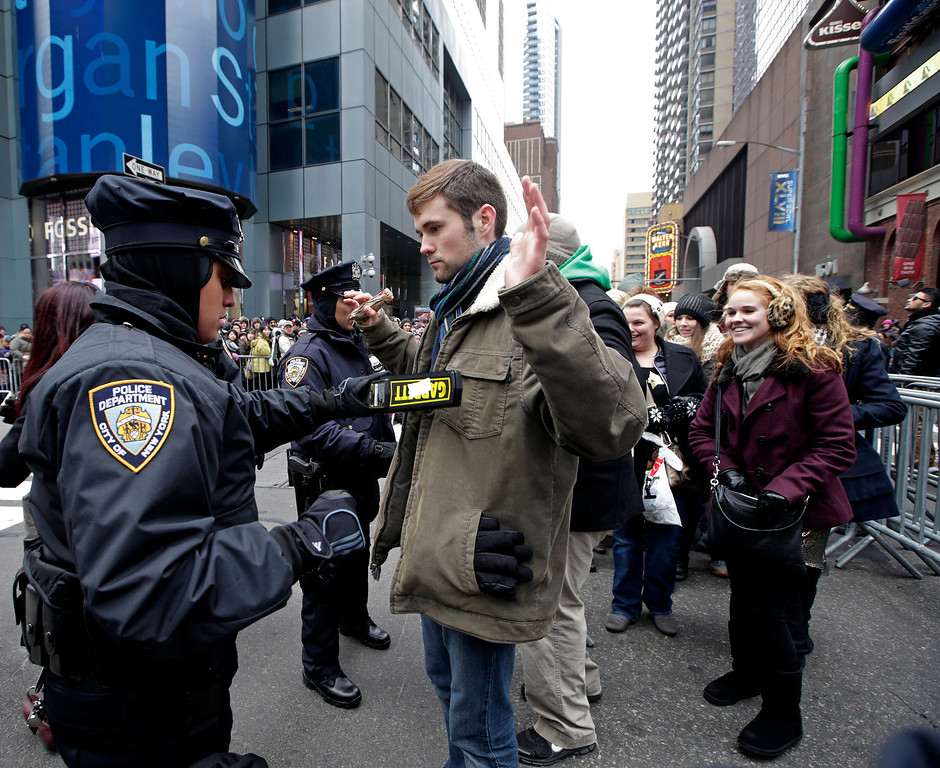 . A New York City police officer uses a metal detector to search a person entering barricaded pens in Times Square on New Year\'s Eve, Tuesday, Dec. 31, 2013, in New York. (AP Photo/Kathy Willens)