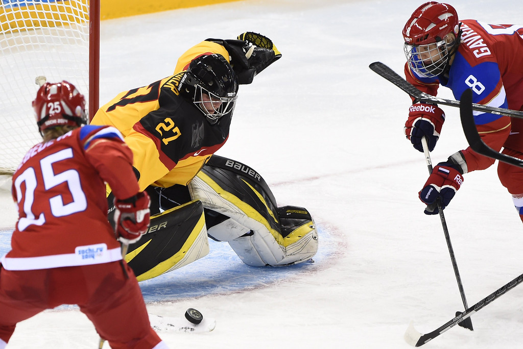 . Russia\'s Yekaterina Lebedeva (L) and Iya Gavrilova try to score against Germany\'s goalkeeper Viona Harrer during a Women\'s Ice Hockey Group B match between Russia and Germany at the Shayba Arena during the Sochi Winter Olympics on February 9, 2014. JONATHAN NACKSTRAND/AFP/Getty Images