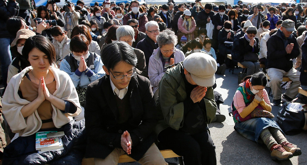 . People observe a moment of silence during a rally at 2:46 p.m. (0546 GMT), the time when the magnitude 9.0 earthquake struck off Japan\'s coast in 2011, in Tokyo March 11, 2013. Japan honored the victims of its worst disaster since World War Two on Monday: the March 11, 2011 earthquake, tsunami and nuclear crisis that killed almost 19,000 people and stranded 315,000 evacuees, including refugees who fled radiation from the devastated Fukushima atomic plant.  REUTERS/Toru Hanai
