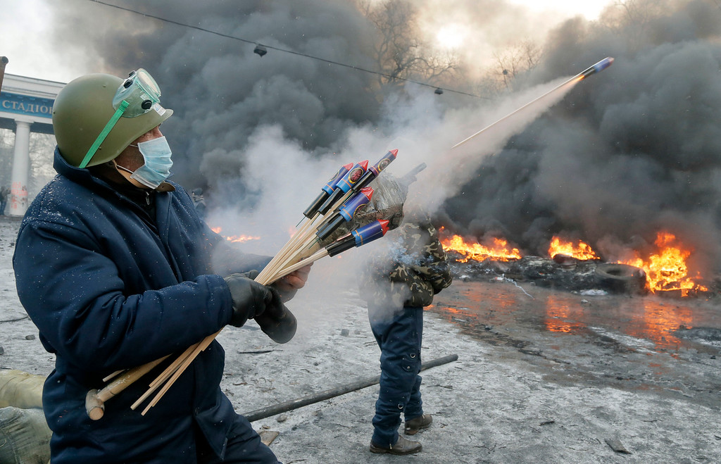 . A protester aims fireworks at police during clashes, in central Kiev, Ukraine, Thursday, Jan. 23, 2014.   (AP Photo/Efrem Lukatsky)