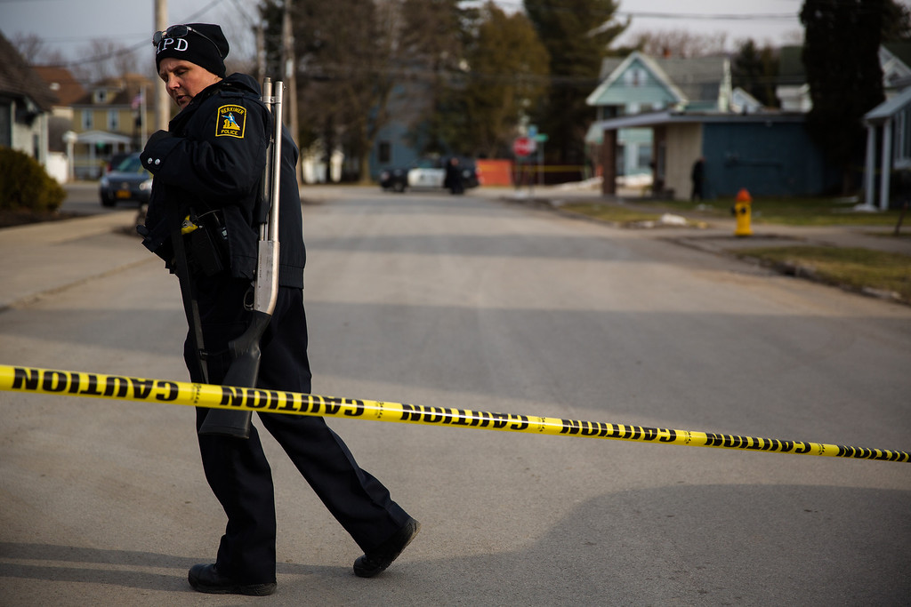. A Herkimer police officer walks the perimeter of the crime scene at Gaffey\'s Fast Lube and Car Wash where a gunman shot and killed two people on March 13, 2013 in Herkimer, New York. (Photo by Brett Carlsen/Getty Images)
