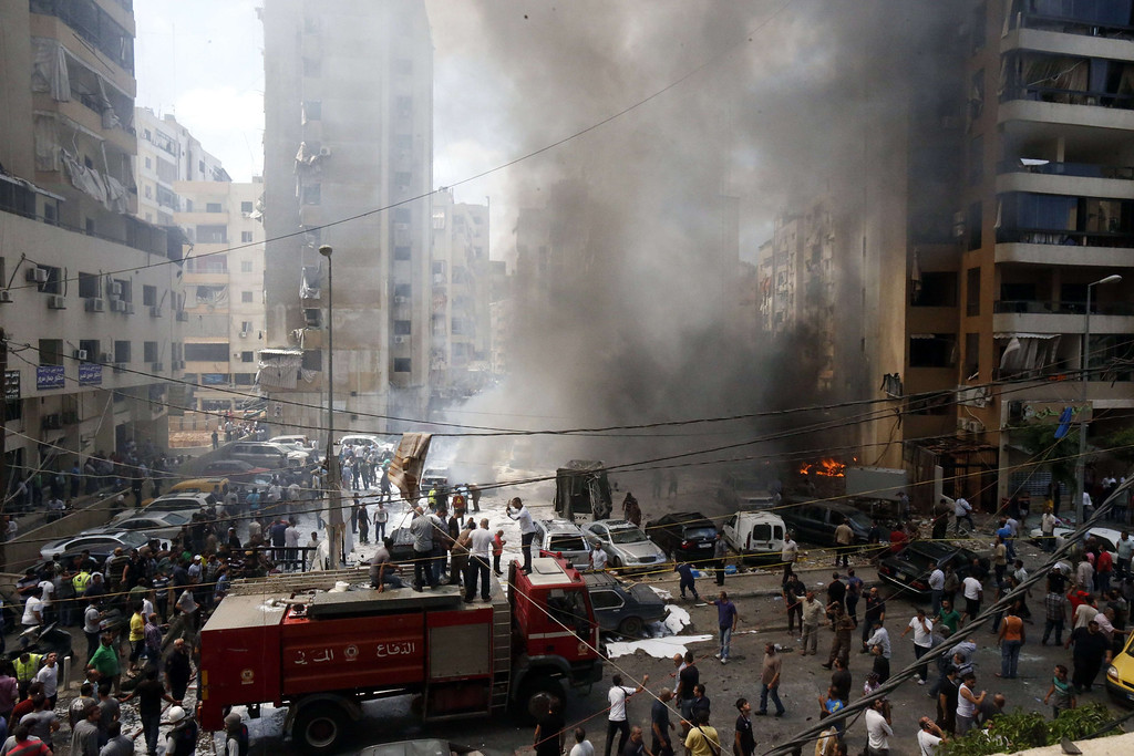 . Firefighters and residents gather at the site of an explosion in Beirut\'s southern suburb neighborhood of Bir al-Abed on July 9, 2013.   AFP PHOTO/STR-/AFP/Getty Images