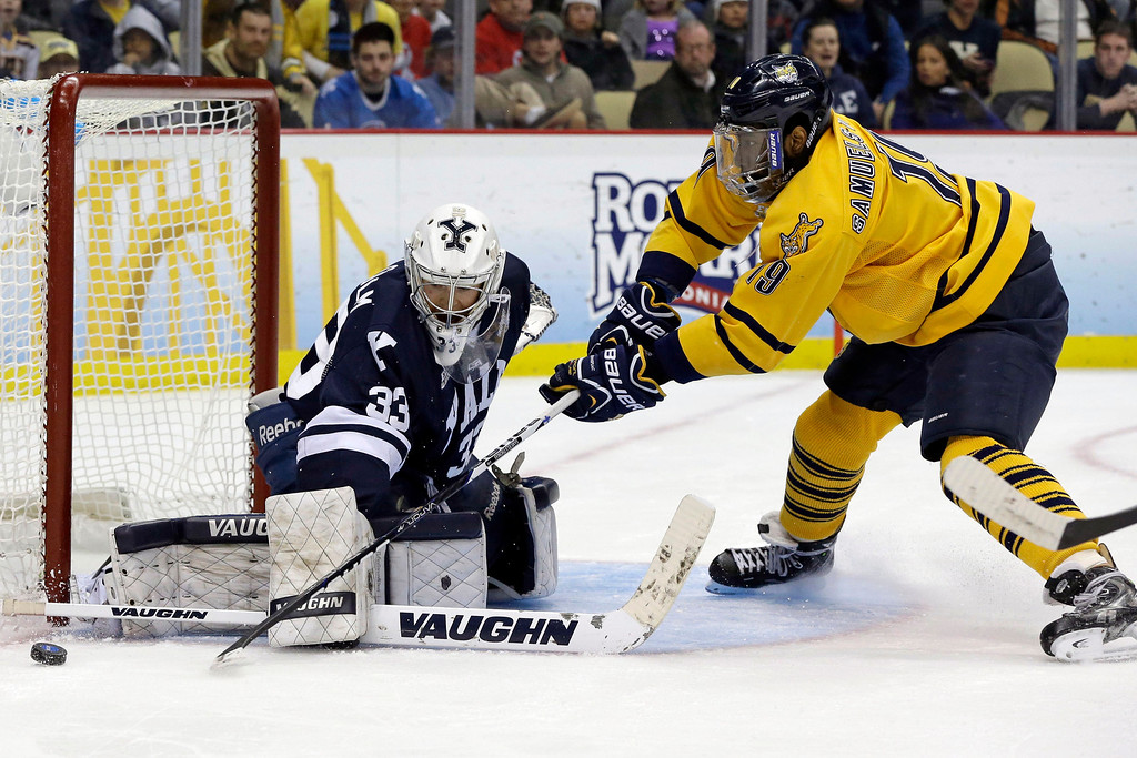 . Quinnipiac\'s Jordan Samuels-Thomas (19)  has a shot blocked by Yale goalie Jeff Malcolm (33) during the first period of the NCAA Frozen Four men\'s college hockey national championship game in Pittsburgh on Saturday, April 13, 2013. (AP Photo/Gene Puskar)