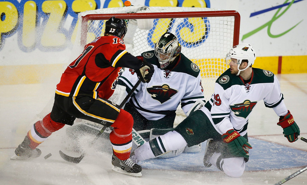 . Minnesota Wild goalie Darcy Kuemper, center, kicks the puck away from Calgary Flames\' Lance Bouma, left, with the help of teammate Stephane Veilleux during the second period of an NHL hockey game in Calgary, Alberta, Saturday, Feb. 1, 2014. (AP Photo/The Canadian Press, Jeff McIntosh)