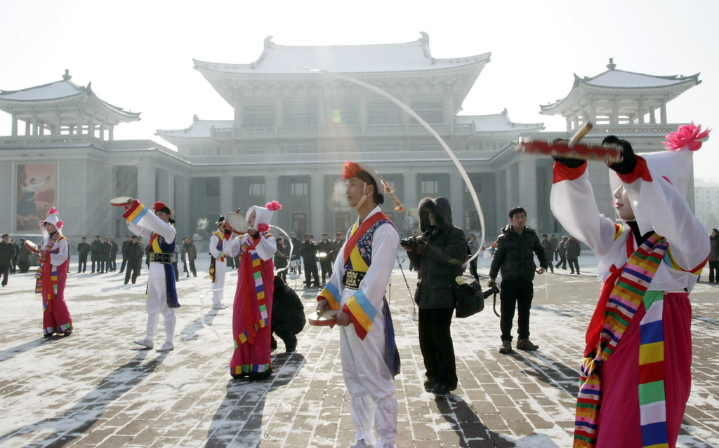. North Korean youths in traditional Korean outfit play instruments in front of the Pyongyang Grand Theatre in Pyongyang, North Korea, to celebrate a rocket launch on Wednesday, Dec. 12, 2012. North Korea appeared to successfully fire a long-range rocket Wednesday, defying international warnings as the regime of Kim Jong Un pushes forward with its quest to develop the technology needed to deliver a nuclear warhead. (AP Photo/Jon Chol Jin)