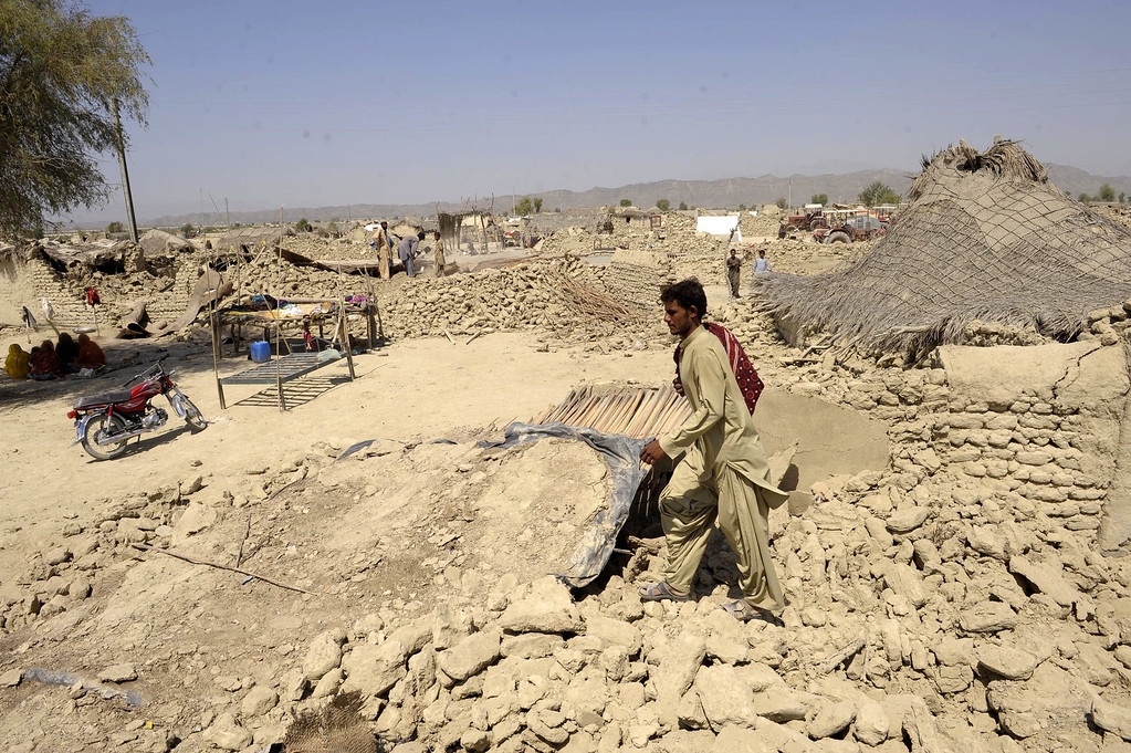 . A Pakistani survivor walks through the debris of destroyed houses in the earthquake-devastated district of Awaran on September 25, 2013.   AFP PHOTO/Banaras KHAN/AFP/Getty Images